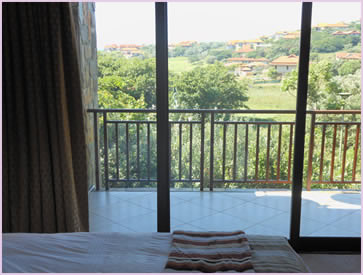 One of the bedrooms of 3 Baluwatu, with a beautiful view of the nearby Zimbali Golf Course and ocean