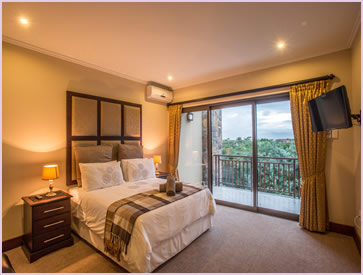 Another view of the main bedroom of the Baluwatu unit at Zimbali Holiday Home, showing it's air conditoner and HD TV